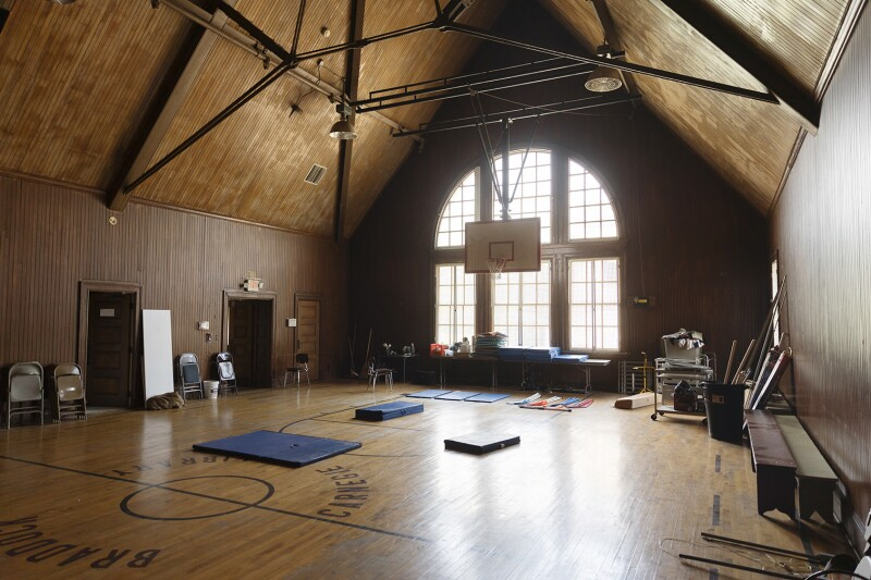 An old indoor basketball court with the hoop hanging from the ceiling.