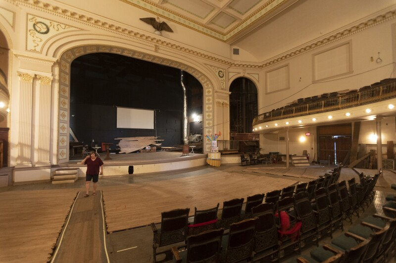The stage of an old theater, with a person walking up the aisle.
