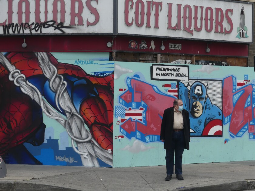 A man wearing a face mask standing on a sidewalk in front of a wall painted with cartoon characters.
