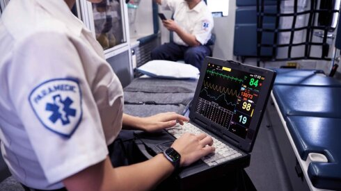 A woman uses a laptop in an ambulance