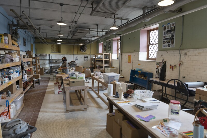 A woman wearing a facemask while working in the Carnegie Library Ceramics Room.