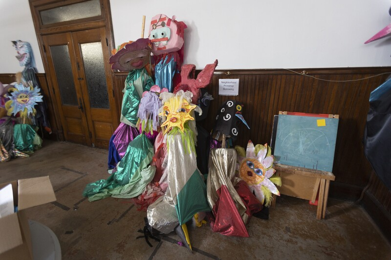 A bunch of large colorful puppets stacked against a wall.